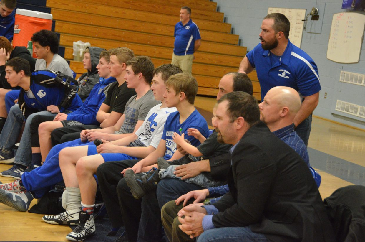 Moffat County High School wrestlers and coaches cheer from the bench Friday night.