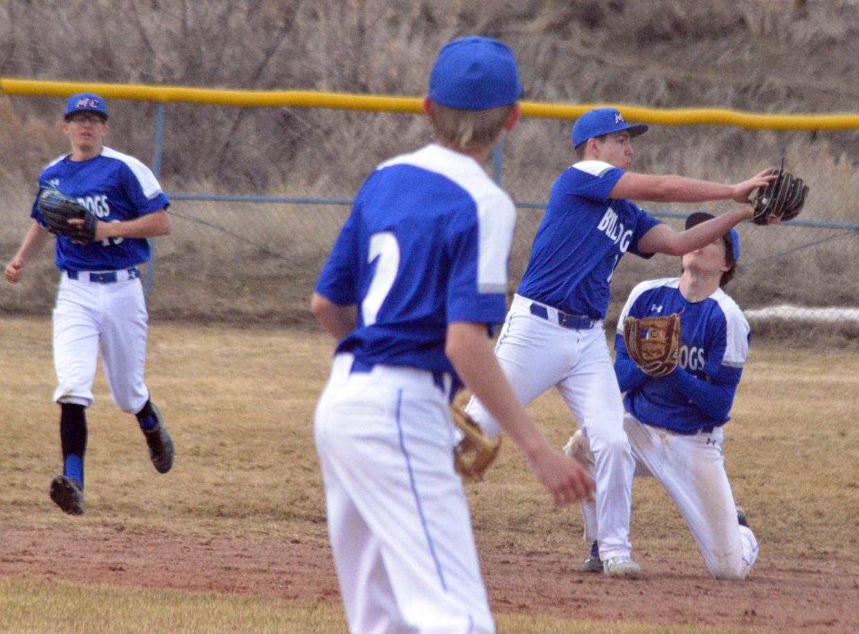 Moffat County High School's Greg Hixson snatches an infield fly while side-stepping teammate Connor Murphy.