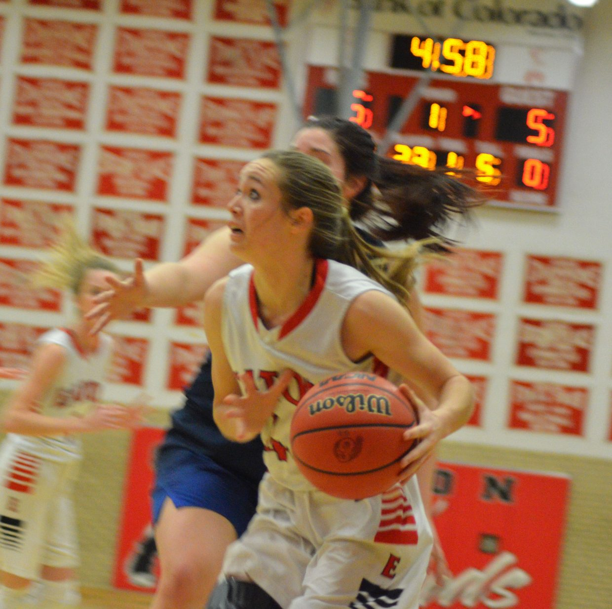 Moffat County High School's Madie Weber edges in beneath the basket against University.