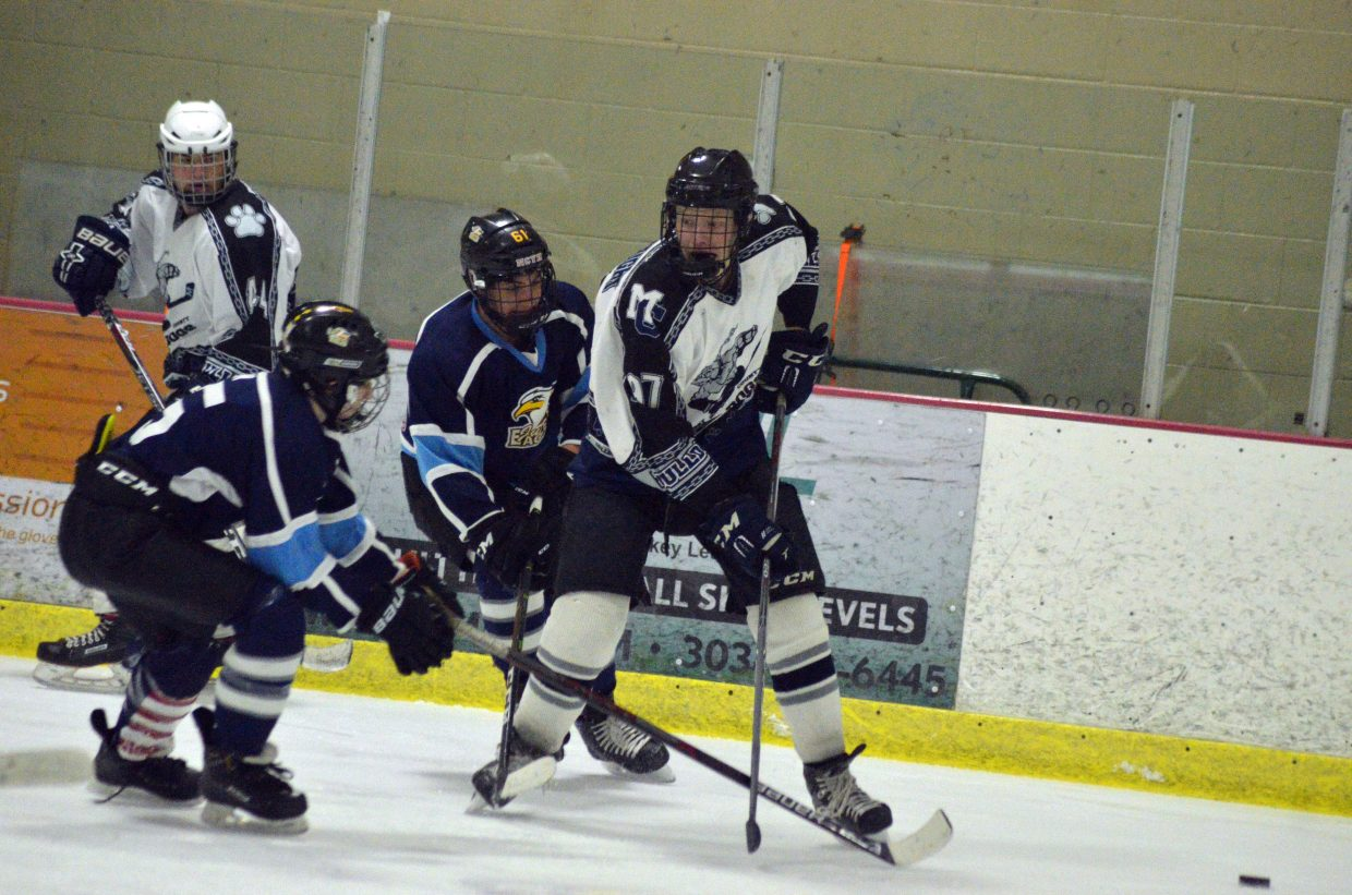 Moffat County Bulldogs' Wyatt Boatright knocks the puck away from Northern Colorado.