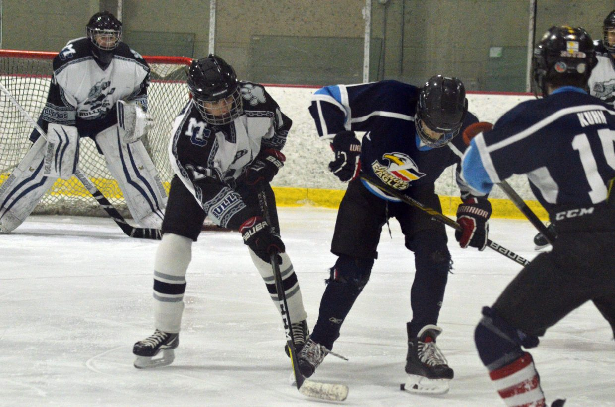Moffat County Bulldogs' Clay Durham works to get the puck free from Northern Colorado.