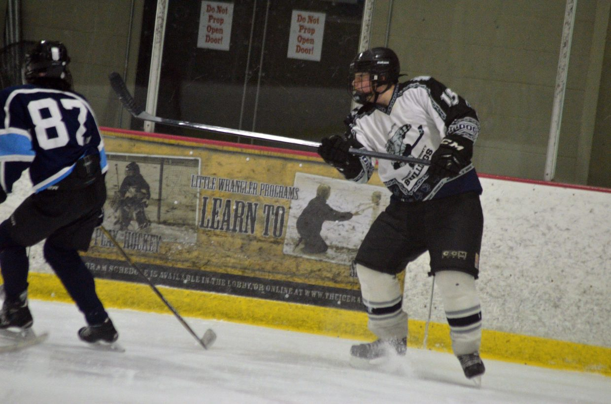 Moffat County Bulldogs' Corey Scranton fires a pass along the boards against Northern Colorado.