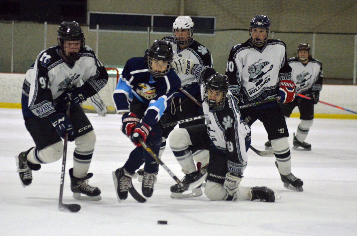 Moffat County Bulldogs hustle after the puck against Northern Colorado at center ice.