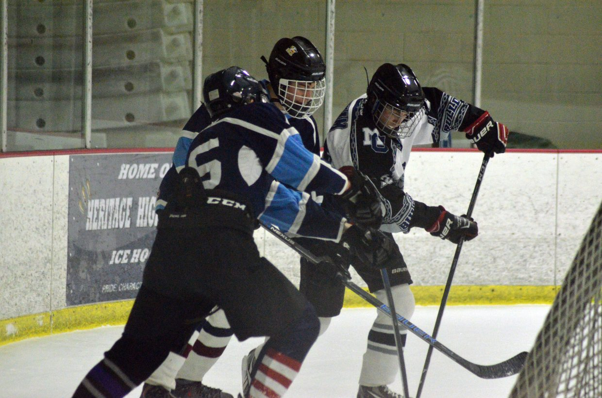Moffat County Bulldogs' Clay Durham digs for the puck behind the Northern Colorado goal.