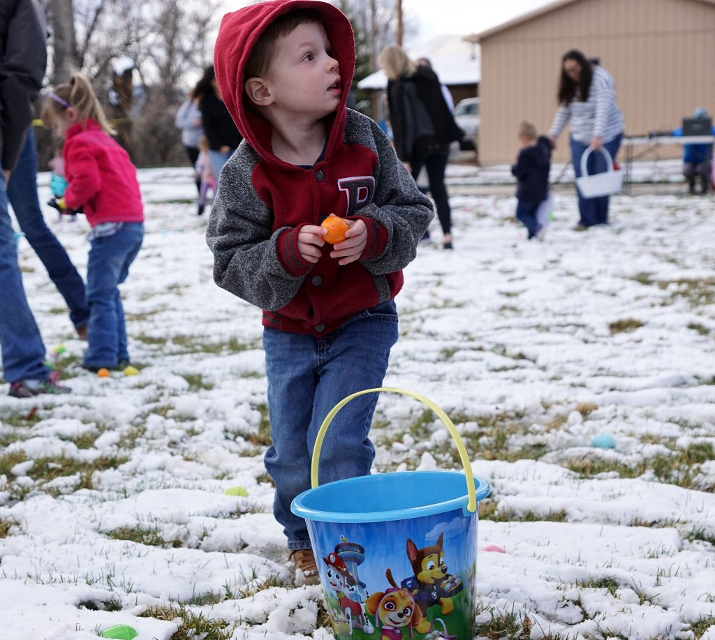 A child listens to his parent after collecting a brightly colored egg.