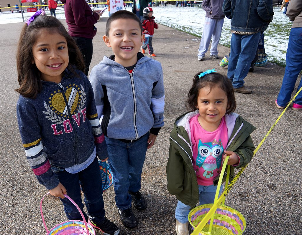 Yileyni, Giovanni and Adelyn Garay-Garcia showing off smiles and empty Easter baskets prior to the start of the hunt for candy filled eggs.