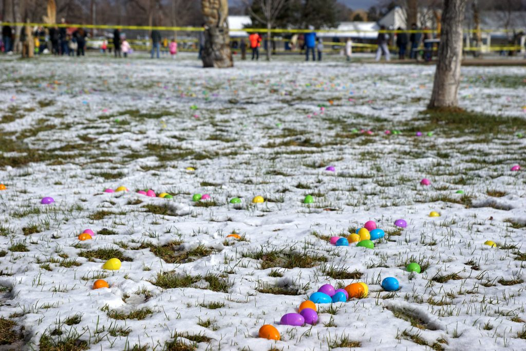 Brightly colored Easter eggs lay in the snow as crowds gather.