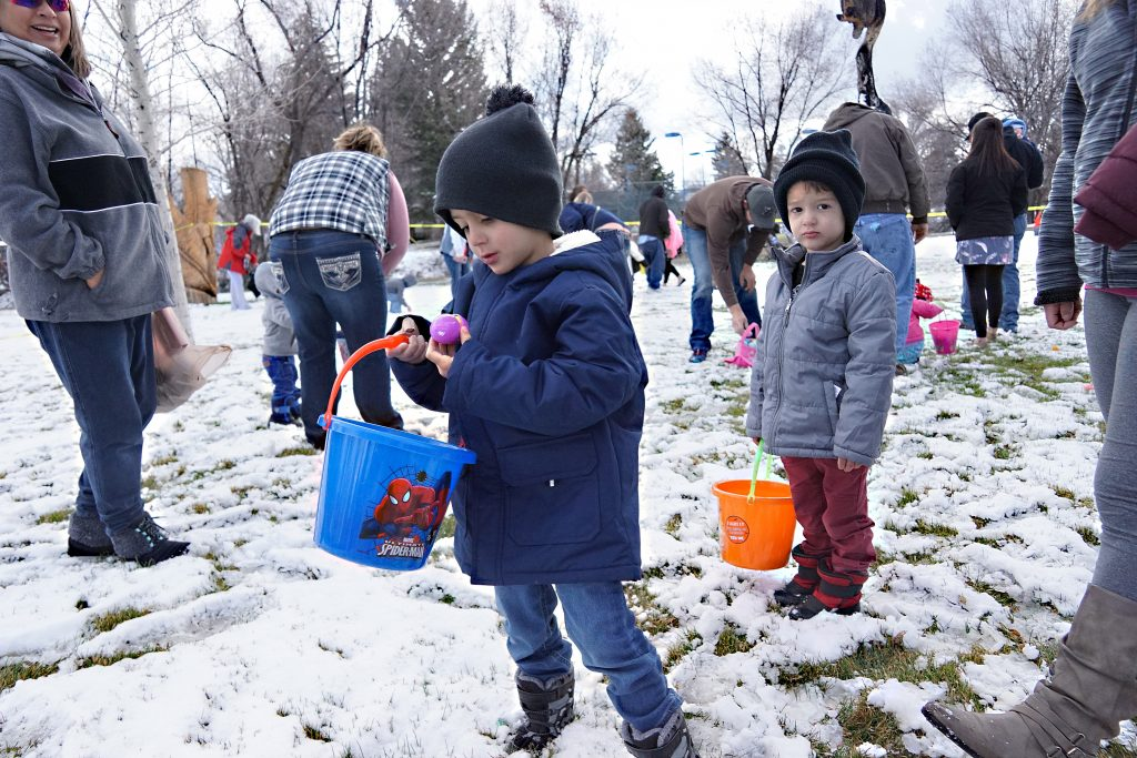 Children bundled up in coats and hats hunt Easter eggs in the snow.