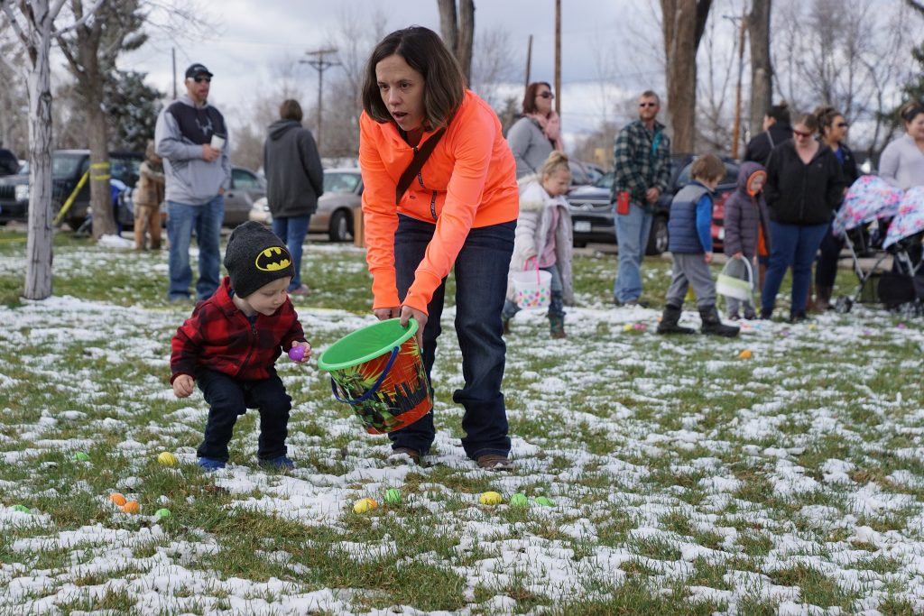 A parent helps her child collect Easter eggs in the section of the park allocated for ages birth to 3-years.