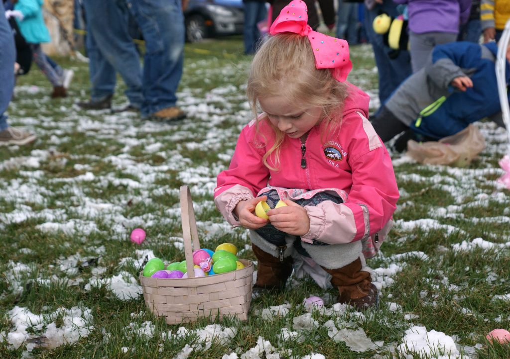 Taking a break from hunting Easter eggs, this kiddo pauses to crack open an egg to see what's inside.