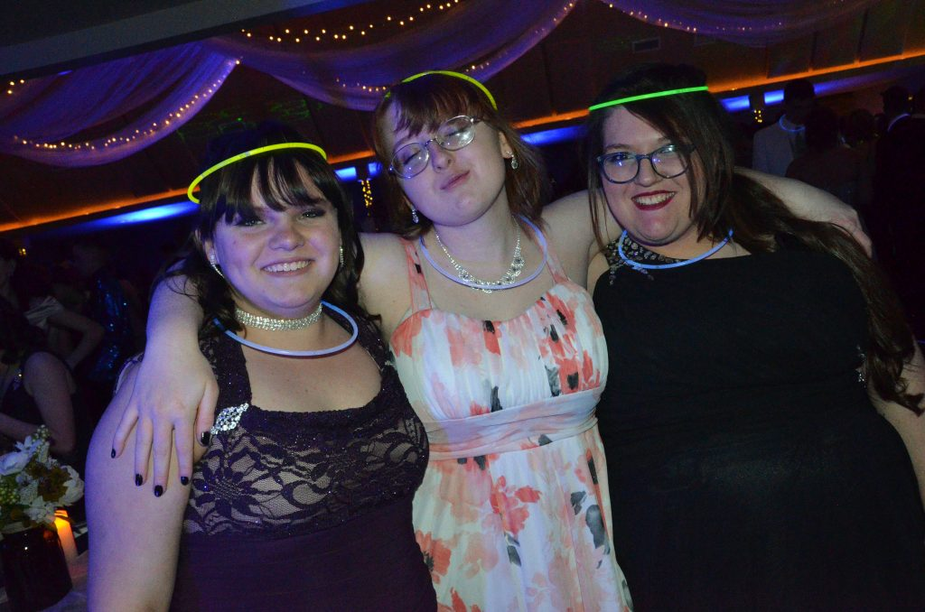 From left, Nikki Brown, Savannah Jacobsen, Orianah Chappele don glow rings during Moffat County High School prom.