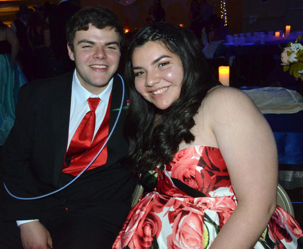 Aaron Hernandez and Hali Reyes take a quick seat from the action at Moffat County high School prom.