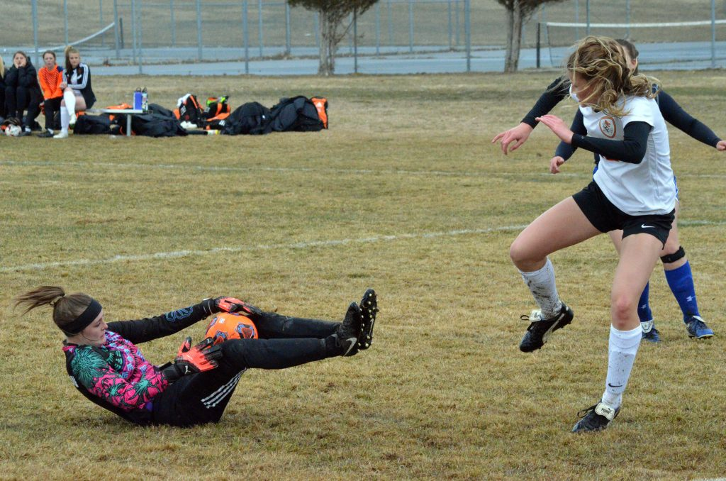 Moffat County High School's Bailey Lawton strips the ball from Grand Junction.