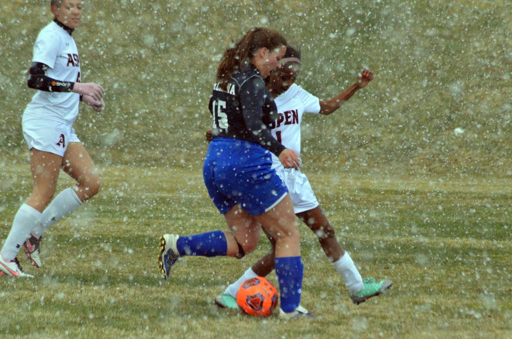 Moffat County High School's Ebawnee Smercina vies for the ball against Aspen as a snow flurry swirls around players.