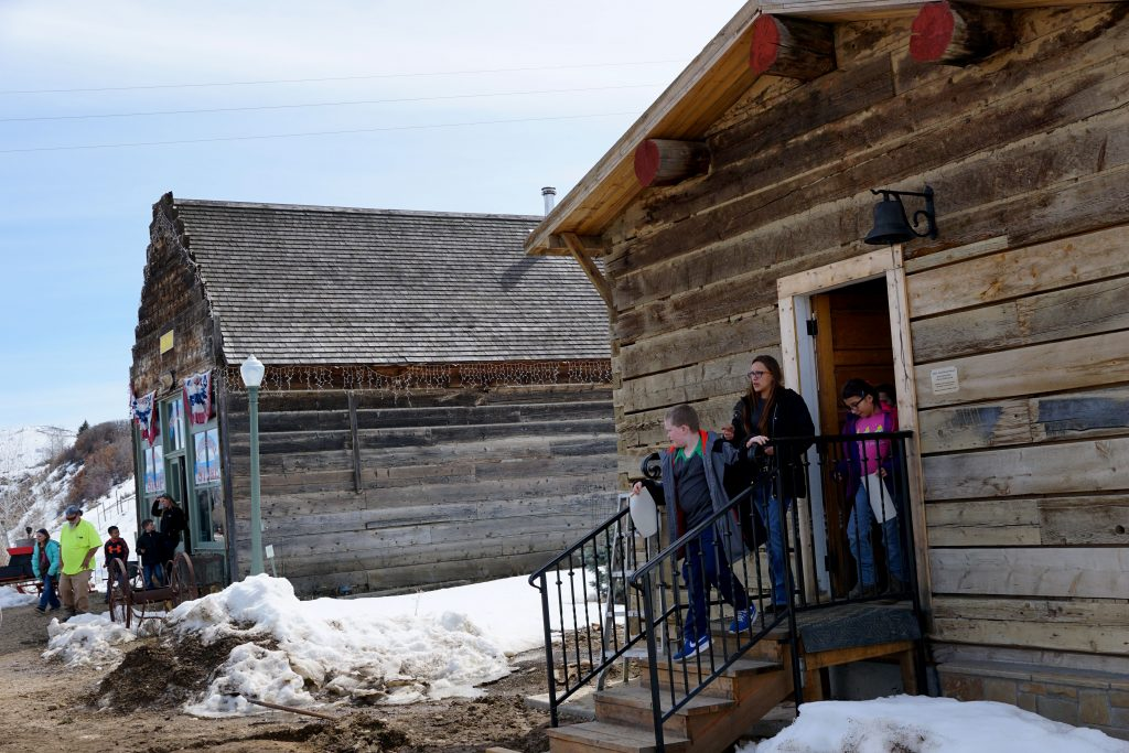 One group of children exit the newly restored, one-room classroom as another group leave the store.