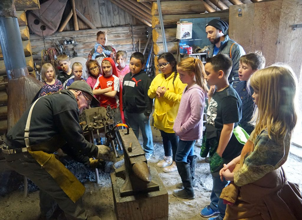 Students watch as blacksmith Terry Carwile demonstrates how metal implements used to be forged.