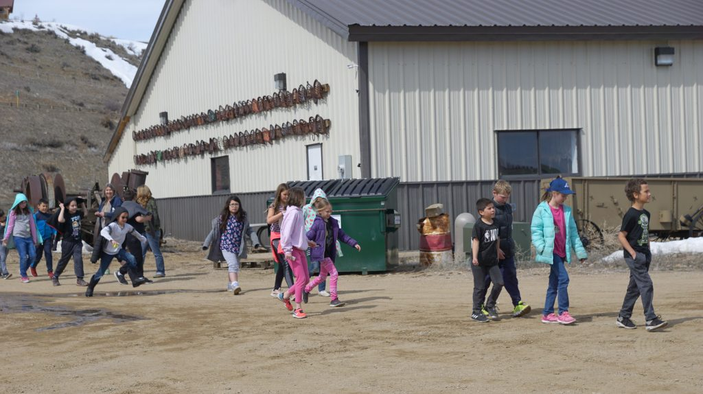 A group of students rotates from a tour of the black smith shop to buses waiting to take them back to school and modern life.